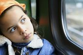 A young girl stares out of the window from a moving train, lost in her little world