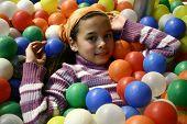 Постер, плакат: Молодая девушка погруженной в шариковой ручкой окруженный красочными пластиковые шарики