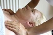A massage therapist giving a shoulder massage to a client, as part of a holistic massage