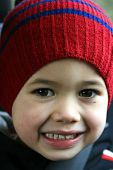 A very happy young boy in red hat, belted in his seat.