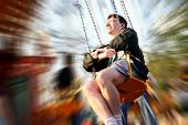 A man reliving his childhood, having a go at the fairground ride with movement blur.