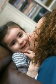 A beautiful little girl enjoys being kissed by her mother. Half saturation rendered with soft filter