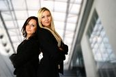 Two caucasian businesswoman standing back to back against interior corporate building. Concept of te