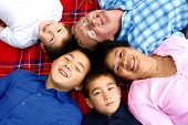 Beautiful family of intermarriage couple from Thailand and caucasian with their three boys in the pa