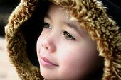 Young boy with fluffy hooded winter coat, feeling the chill in the air, outdoors. poster
