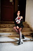 Young Goth Girl On Black Leather Skirt And Jacket With Backpack Posed On Stairs Of Old House. poster