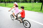 Two young children riding on a tandem bike.