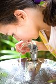 Young girl quenching thirst from the cool water fountain, outdoor