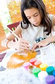 Young girl painting a paper plate in arts and craft.