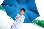 Menino bonito com pé grande guarda-chuva na praia na chuva