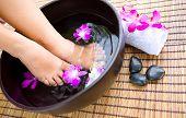 Mujer-Spa de pies en un recipiente de agua perfumada floral en spa