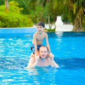 Man with young son enjoying some games in the swimming pool