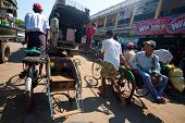 PATHEIN MYANMAR - JAN 30: Trishaw operators ferry locals from market January 30, 2010 in Pathein, Myanmar. This is the most common method of transport that's cheap and convenient.