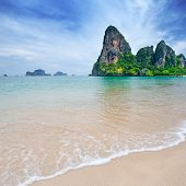Beautiful beach with crystal clear blue waters of the Andaman sea against blue sky at Krabi bay, Thailand