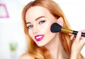 Beauty woman applying makeup. Beautiful girl looking in the mirror and applying cosmetic with a big  poster