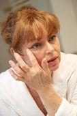 Portrait of senior woman applying moisturizing cream