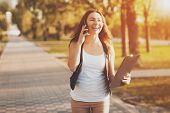 Young Girl Talking On A Cell Phone In The Park. Smiling Beautiful Girl Walking In The Park Talking O poster