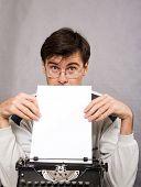 man with vintage typewriter and white paper sheet