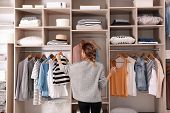 Woman Choosing Outfit From Large Wardrobe Closet With Stylish Clothes And Home Stuff poster