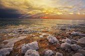 Costa do mar morto em Israel um trovão-tempestade de Primavera. As pedras costeiras cobertas por adjou salgado
