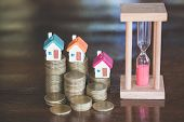 Mini House On Stack Of Coins,money And House,  Mortgage, Savings Money For Buy House And Loan To Bus poster