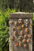 Stone curbstone in a garden, decorated ceramic ritual masks