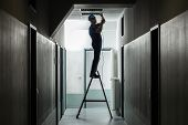 Silhouette Of A Male Electrician On Step Ladder Installing Light At Corridor poster