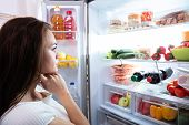 Pretty Woman Looking For Food In Refrigerator poster