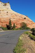 A bright sunny day in Zion National Park. Excellent road winds sharply between the picturesque hills