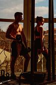 Man And Woman In Sportswear In Gym, Window On Background. Couple Does Physical Exercises With Dumbbe poster