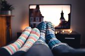 Couple With Socks And Woolen Stockings Watching Movies Or Series On Tv In Winter. Woman And Man Sitt poster