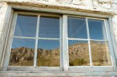 Guadalupe Ranch House window reflection of mountains