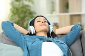 Relaxed Woman Resting Listening To Music Sitting On A Couch In The Living Room At Home poster