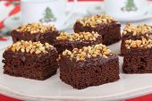 stock photo of chocolate fudge  - Brownies with chocolate nut frosting on a platter with Christmas cups in background