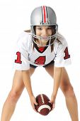 A beautiful teen  in a football helmet, shirt and shorts looking up from preparing to toss a football from between her knees.  On a white background.