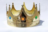 A Genuine Plastic King or Queen crown in Gold Plastic with Colorful Plastic Jewels isolated on white