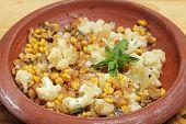 Coliflor y maíz dulce casero balti curry en un recipiente de terracota India