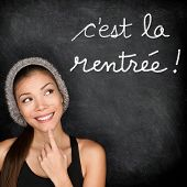 Cest la Rentree Scolaire - French college university student woman thinking Back to School written in French on blackboard by female on chalkboard. French language at college or high school.