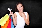 Shopping woman thinking with bags on blackboard background. Shopper girl holding credit card and sho