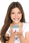Buying new home concept - woman holding mini house. House mortgage and happy home owner conceptual image with multi-ethnic Asian Chinese / Caucasian female model isolated on white background.