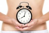 Biological clock ticking - woman holding clock in front of stomach. Biological clock and pregnancy concept with female hands and belly.