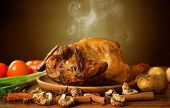 Whole roasted chicken with vegetables, on wooden tray fresh from oven with hot steam smoke, brown background