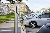 stock photo of fuel efficiency  - Silver Electric Cars Plugged into Free Recharging Station - JPG