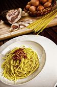 Italian traditional recipe, spaghetti alla carbonara with ingredients on background and a glass of red wine