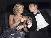 stock photo of limousine  - Happy young glamorous couple toasting champagne in limousine - JPG