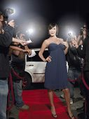 Full length of young female celebrity posing on red carpet surrounded by paparazzi