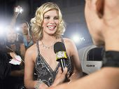 Beautiful young celebrity being interviewed by journalist at premiere