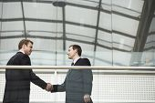 Businessmen shaking hands while standing against glass railing in office