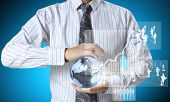 holding glowing earth globe and  financial symbols coming from hand