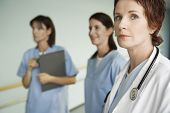 Serious female physician with two nurses in hospital corridor